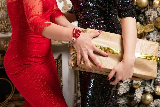 Weibliche hände, die für weihnachtsgeschenkboxen mit tannenbaum auf hintergrund kämpfen.