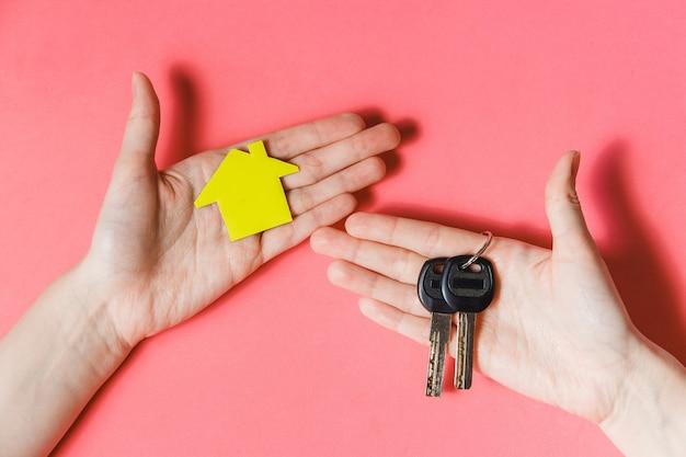 Weibliche hände, die gelbes papierhaus und schlüssel halten