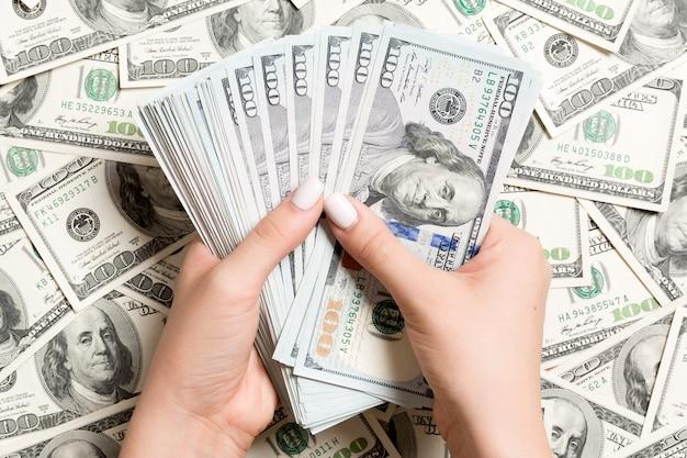 Weibliche hände, die geld auf dollar zählen