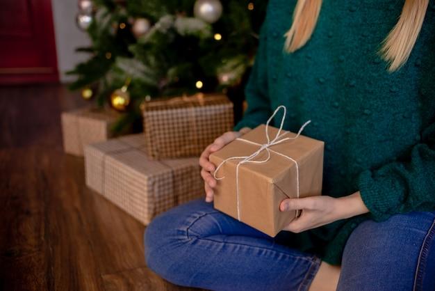 Weibliche hände, die geschenk halten. geschenk mit bastelpapier umwickelt. oberster horizontaler ansichtfeiertagskonzept copyspace.