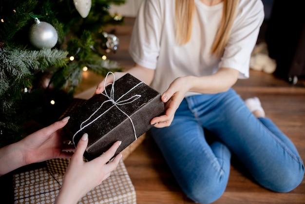 Weibliche hände, die geschenk halten. geschenk mit bastelpapier umwickelt.