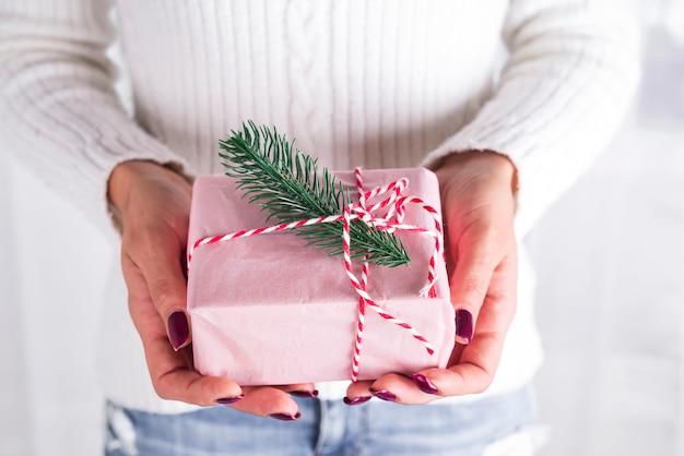 Weibliche hände, die geschenk mit rotem bogen auf weiß halten. festliche kulisse für den urlaub