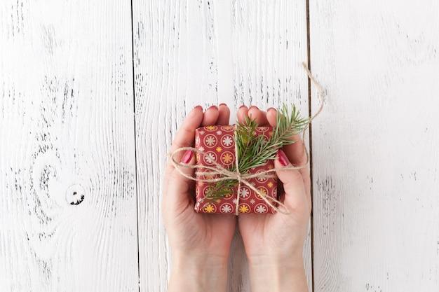 Weibliche hände, die geschenk mit schnurbogen auf weißer rustikaler oberfläche halten