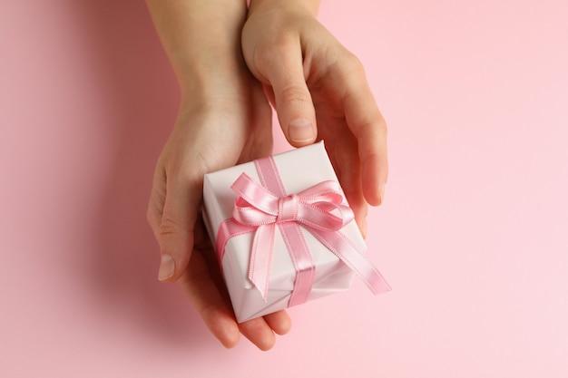Weibliche hände, die geschenkbox auf rosa hintergrund halten