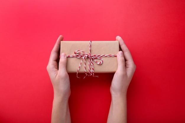 Weibliche hände, die geschenkbox auf rotem hintergrund halten