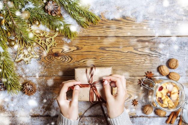 Weibliche hände, die geschenkbox auf weihnachtshintergrund öffnen