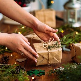Weibliche hände, die geschenkbox des feiertagshandwerks mit tannenzweig auf dem holztisch halten