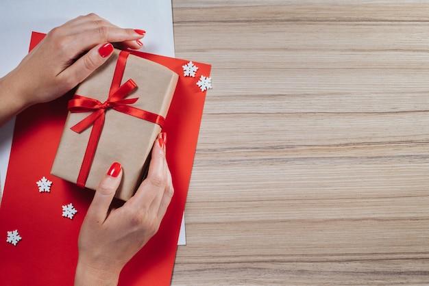 Weibliche hände, die geschenkbox halten, eingewickelt in bastelpapier und verziert mit rotem satinband auf hölzernem hintergrund