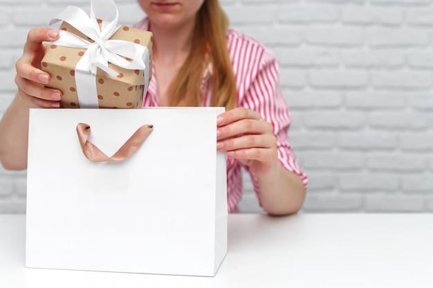 Weibliche hände, die geschenkbox halten.