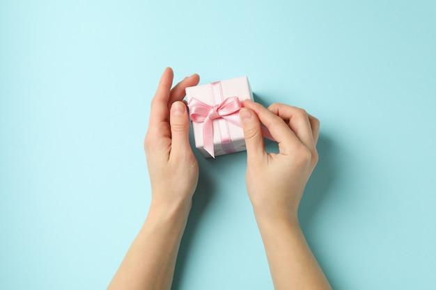 Weibliche hände, die geschenkbox mit rosa band auf blauem hintergrund halten