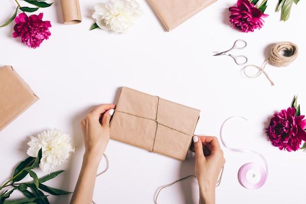Weibliche hände, die geschenke auf weißem tisch einwickeln