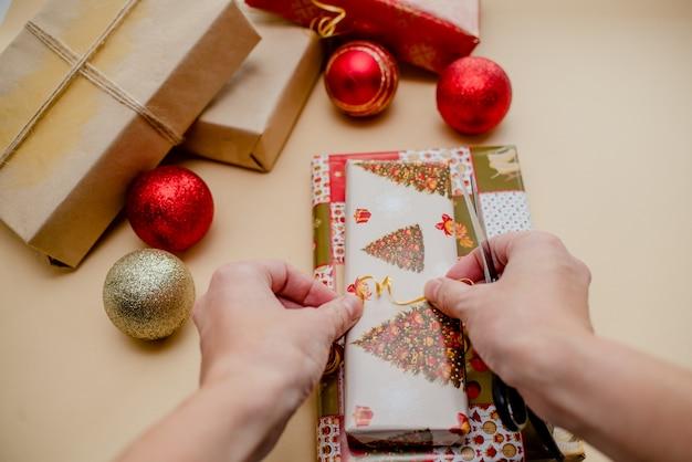 Weibliche hände, die geschenke halten und geschenke verpacken