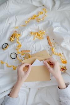 Weibliche hände, die geschenkkarte, umschlag und geschenkbox über der bettdecke halten. neujahr und weihnachten konzept. horizontale ansicht von oben