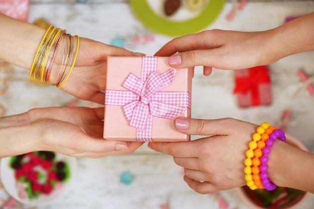 Weibliche hände, die geschenknahaufnahme halten