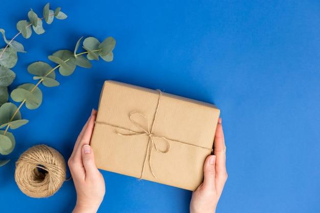 Weibliche hände, die geschenkverpackung und eukalyptusblätter auf blauer oberfläche halten