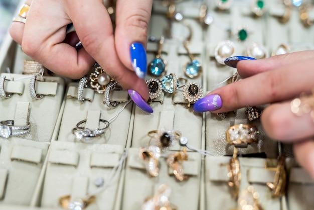 Weibliche hände, die goldenen schmuck im shop zeigen