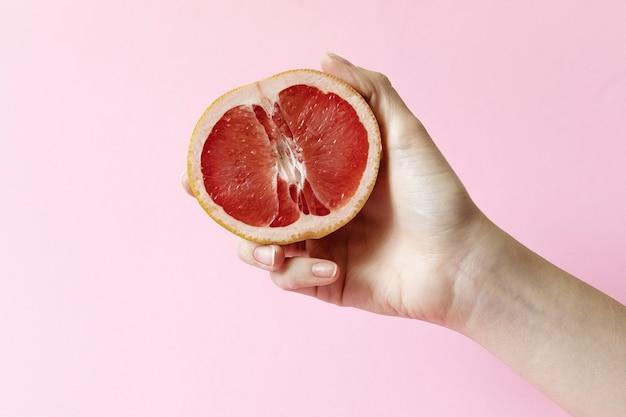 Weibliche hände, die halbe grapefruit auf rosa hintergrund halten, weibliches masturbationskonzept