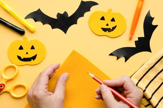 Weibliche hände, die halloween-dekorationen malen. handgemachter kürbis, schwarze fledermaus, spinne auf orange oberfläche.