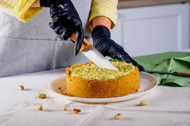 Weibliche hände, die hausgemachten pistazienkäsekuchen auf dem tisch schneiden