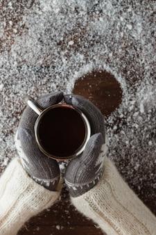Weibliche hände, die heißen kaffee über holztisch halten. draufsicht mit kopierraum