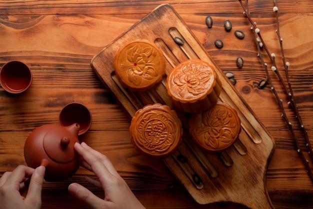 Weibliche hände, die heißen tee mit traditionellen mondkuchen auf holztablett gießen. das chinesische schriftzeichen auf dem mondkuchen steht auf englisch für