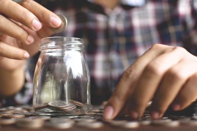Weibliche hände, die herein das geld zum glasgefäß auf planke fallenlassen, fangen an, geld zu planen und zu sparen.