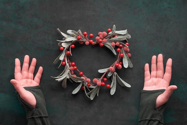 Weibliche hände, die herzförmigen dekorativen mistelweihnachtskranz mit roten beeren zeigen, flache lage