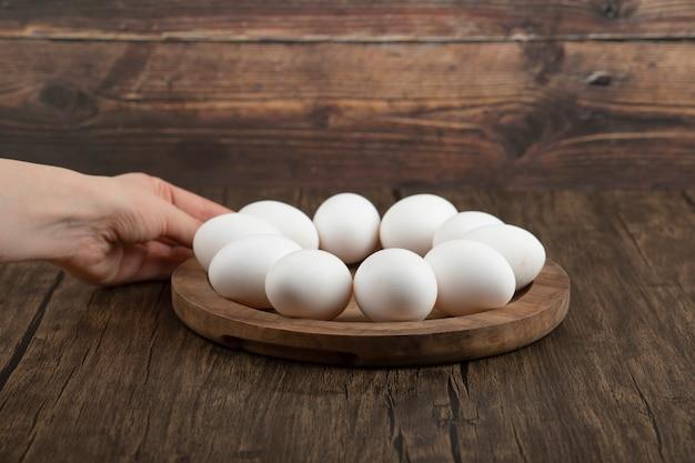 Weibliche hände, die holzbrett mit rohen eiern auf hölzerner oberfläche halten.