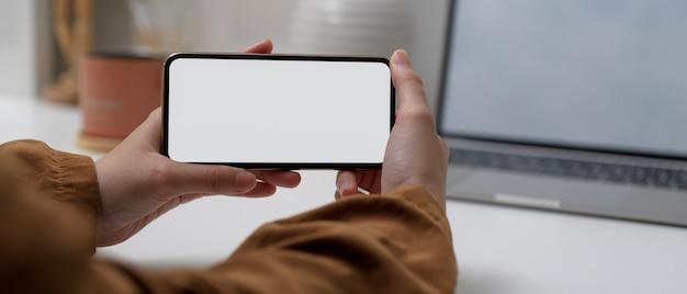 Weibliche hände, die horizontales modell-smartphone halten, während sie am arbeitstisch mit modell-laptop sitzen