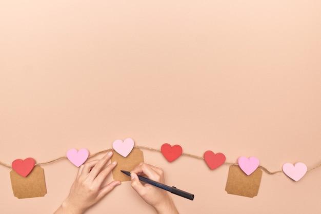 Weibliche hände, die in karten auf einem valentinstagherzenhintergrund schreiben