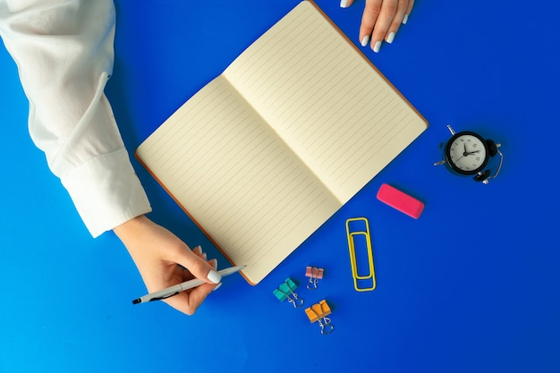 Weibliche hände, die in notizbuch schreiben