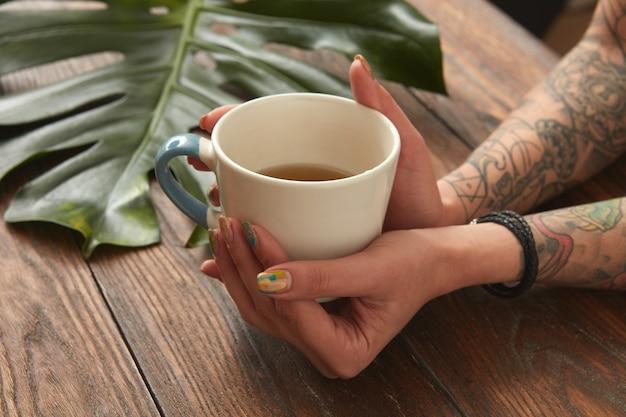 Weibliche hände, die kaffee-espresso in einer weißen tasse auf einem alten hölzernen hintergrund mit einem grünen blatt halten