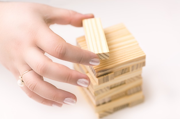 Weibliche hände, die kleines hölzernes turmhaus von wodden block für kinder errichten.
