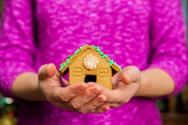 Weibliche hände, die kleines lebkuchenhaus auf tisch mit weihnachtsdekorationen halten