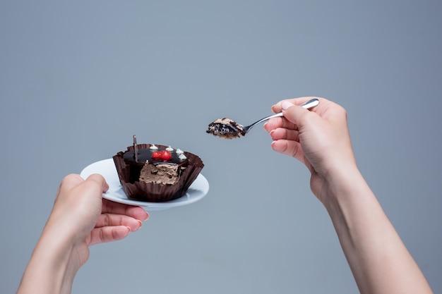 Weibliche hände, die kuchen mit löffel auf grau halten