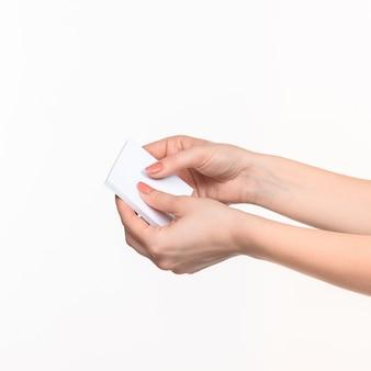 Weibliche hände, die leeres papier für aufzeichnungen halten
