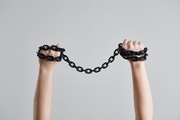 Weibliche hände, die metallmetallkette über kopf halten