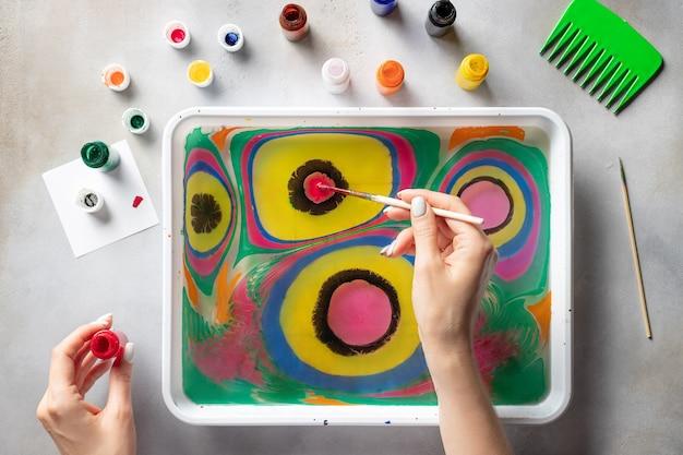 Weibliche hände, die mit farben auf wasser zeichnen. ebru kunst