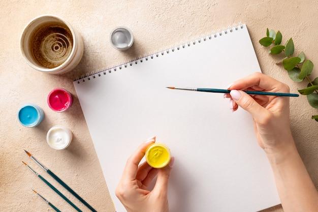 Weibliche hände, die mit farben im skizzenbuch zeichnen
