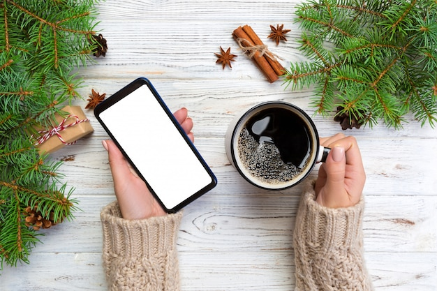 Weibliche hände, die modernen smartphone und becher kaffee halten