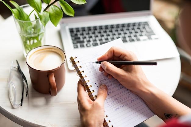 Weibliche hände, die notizbuch und stift halten, während sie arbeitsnotizen am tisch im café machen und frischen cappuccino haben