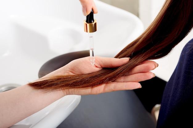 Weibliche hände, die ölserum auf braunes haar der langen frau zur behandlung auftragen. haarpflegekosmetik, bad beauty spa produkte