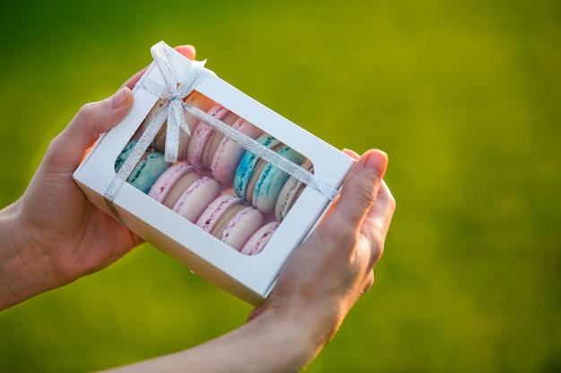 Weibliche hände, die pappgeschenkbox mit bunten rosa blauen handgemachten macaron plätzchen auf grün unscharfem kopienraumhintergrund halten.