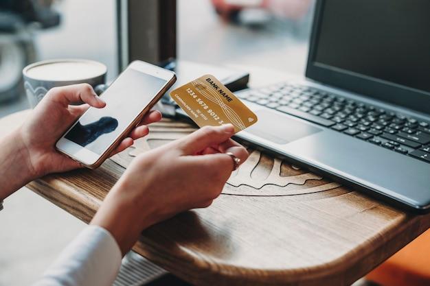 Weibliche hände, die plastikkreditkarte halten und smartphone verwenden. online-shopping mit smartphone beim sitzen in einem café.