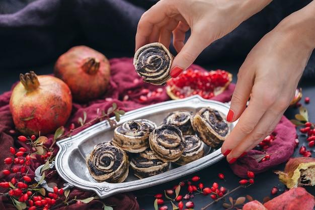 Weibliche hände, die rohe vegane welpenrolle von einer metallplatte mit hagebutten und granatapfelkernen nehmen