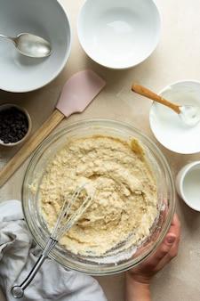 Weibliche hände, die rohen teig mischen, bundt-kuchen in glasschüssel kochen, draufsicht. schritt für schritt rezept.