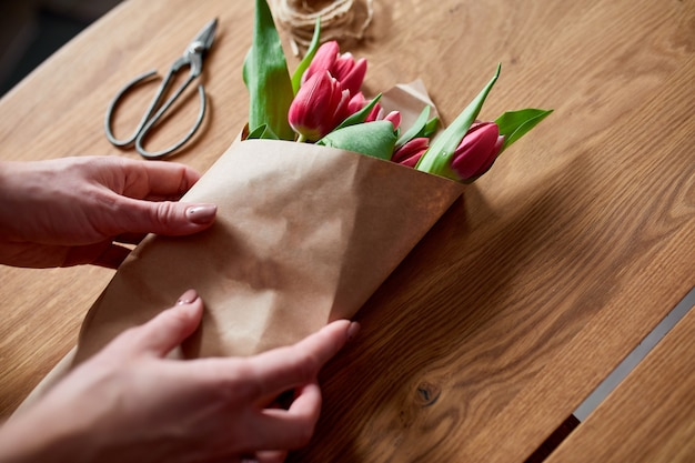 Weibliche hände, die rosa tulpenblumenstrauß auf holztisch arrangieren, floristischer hobbyarbeitsplatz, geschäft, diy, frühlingsgeschenkkonzept, von oben.