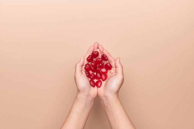 Weibliche hände, die rote herzförmige bonbons für valentinstag halten
