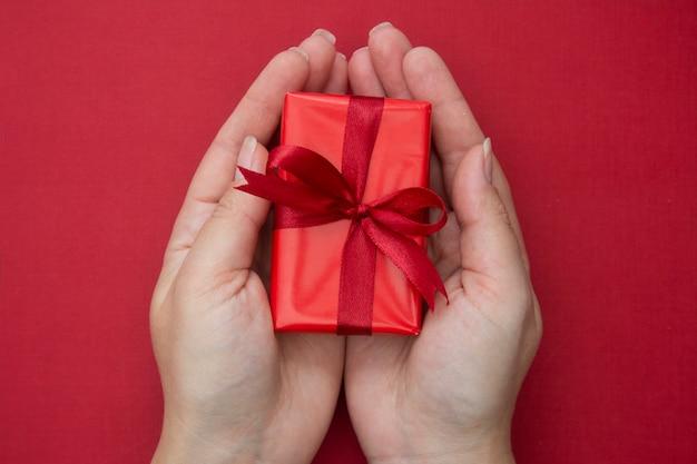 Weibliche hände, die rote weihnachtsgeschenkbox mit rotem band und bogen, über rotem hintergrund halten.