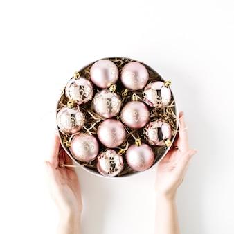 Weibliche hände, die runden kasten mit hellen weihnachtskugeln auf weißem hintergrund halten. flach liegen, draufsicht